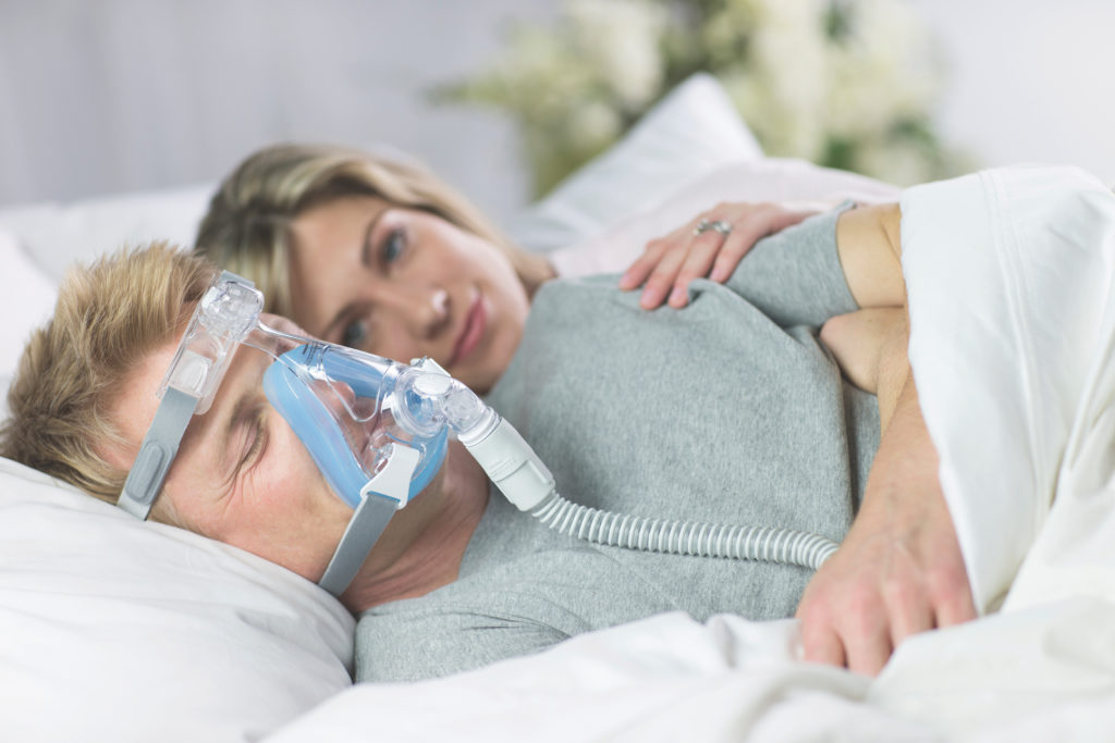 cpap machine prices image of man sleeping next to woman with cpap machine